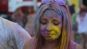 Donna graziosa che tocca il suo fronte coperto nella polvere di colore e che sorride, fest di Holi stock footage