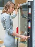 Donna graziosa che usando il distributore automatico immagine stock