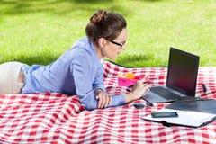 Donna graziosa che utilizza il suo computer portatile nel parco Fotografia Stock Libera da Diritti