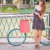Donna graziosa con gli insetti facendo uso del telefono cellulare vicino alla bicicletta d'annata Fotografie Stock