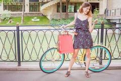 Donna graziosa con gli insetti facendo uso del telefono cellulare vicino alla bicicletta d'annata Immagini Stock Libere da Diritti