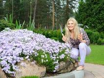 Donna graziosa con gli strumenti di giardinaggio all'aperto Immagine Stock