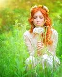 Donna graziosa con i fiori del dente di leone Fotografie Stock Libere da Diritti