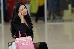 Donna graziosa con i sacchetti della spesa che parla sul telefono cellulare nel centro commerciale fotografia stock libera da diritti