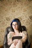 Donna graziosa con i tatuaggi in una presidenza di cuoio immagine stock libera da diritti