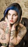 Donna graziosa con i tatuaggi in una presidenza di cuoio fotografia stock