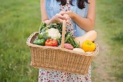 Donna graziosa con il canestro di veg Immagine Stock