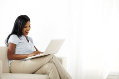 Donna graziosa con il computer portatile sul sofà Fotografie Stock