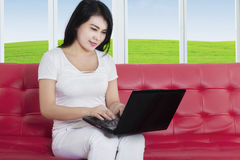 Donna graziosa con il computer portatile sul sofà accogliente Immagine Stock
