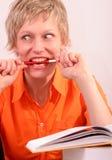 Donna graziosa con il libro che morde una penna Immagine Stock