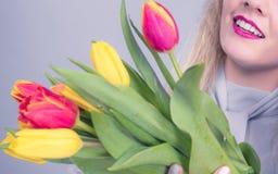 Donna graziosa con il mazzo giallo rosso dei tulipani Fotografia Stock