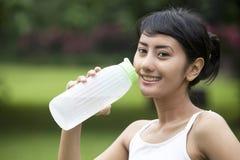 Donna graziosa con una bottiglia di acqua minerale Immagini Stock Libere da Diritti