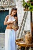 Donna graziosa in costume tradizionale piega Mediterraneo etnico che tiene una brocca dell'olio d'oliva del rattan Ospitalità e c fotografia stock