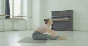 Donna graziosa degli Yogi che pratica esercizio di andata della curvatura