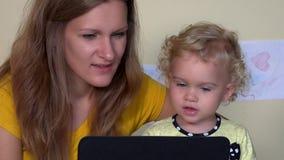 Donna graziosa della babysitter e piccolo bambino che per mezzo del computer della compressa video d archivio