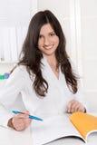 Donna graziosa di affari che sorride allo scrittorio nel suo ufficio Fotografie Stock Libere da Diritti