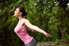 Donna graziosa di misura che fa yoga in parco Fotografie Stock