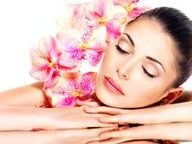 Donna graziosa di rilassamento con pelle sana ed i fiori rosa Fotografie Stock Libere da Diritti