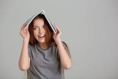 Donna graziosa divertente che sta e che ride con il libro sulla testa Immagine Stock Libera da Diritti
