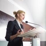 Donna graziosa e giovane di affari che dà una presentazione immagini stock