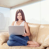 Donna graziosa felice che per mezzo del computer portatile Fotografia Stock
