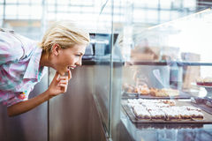 Donna graziosa imbarazzata che esamina i dolci della tazza Fotografia Stock