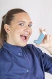 Donna graziosa, infermiere, facendo uso dell'inalatore di asma Immagine Stock Libera da Diritti
