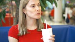 Donna graziosa in maglietta rossa che si siede in caffè che mangia le patate fritte e che beve cola dalla tazza di carta video d archivio