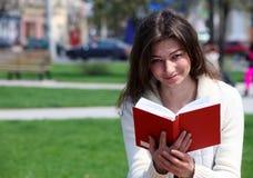 Donna graziosa nel libro e nel sorridere di lettura della sosta Immagine Stock