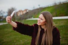 Donna graziosa nel parco con il cellulare immagini stock