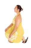 Donna graziosa nell'inginocchiamento giallo del vestito Fotografia Stock