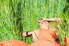 Donna graziosa nella menzogne arancio del vestito Fotografie Stock Libere da Diritti