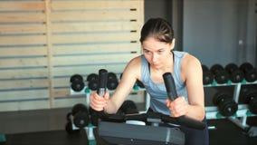 Donna graziosa nella palestra, esercitante le sue gambe che fanno cardio addestramento sulla bicicletta archivi video