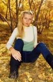 Donna graziosa nella sosta di autunno. Immagine Stock