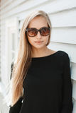Donna graziosa in occhiali da sole vicino ad una parete di legno Fotografia Stock