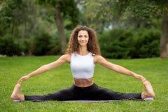 Donna graziosa sorridente che fa gli esercizi di yoga Immagini Stock Libere da Diritti