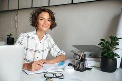 Donna graziosa sorridente che lavora dalla tavola Fotografia Stock Libera da Diritti