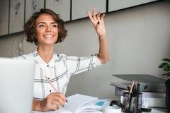 Donna graziosa sorridente che si siede dalla tavola Immagine Stock