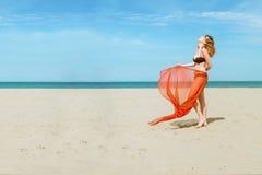 Donna graziosa sui sarong d'uso del tessuto di seta della spiaggia Fotografia Stock