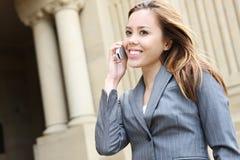 Donna graziosa sul telefono delle cellule al banco Fotografia Stock