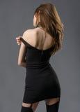Donna graziosa in un mini vestito nero Fotografie Stock