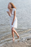 Donna graziosa in un vestito bianco sulla costa Fotografie Stock