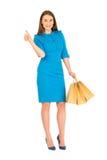 Donna graziosa in vestito blu che posa con le borse Immagine Stock