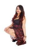 Donna graziosa in vestito che si accovaccia sul pavimento Fotografia Stock