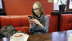 Donna graziosa in vetri facendo uso del app sullo smartphone in caffè che sorride e che manda un sms sul telefono cellulare Bello stock footage