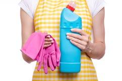 Donna in grembiule in mani che puliscono i prodotti chimici di famiglia detergenti della toilette domestica e del guanto Fotografia Stock