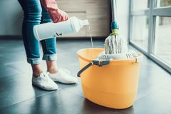 Donna in guanti che prepearing per pulire pavimento con la zazzera immagine stock
