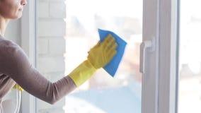 Donna in guanti che puliscono finestra con lo straccio stock footage