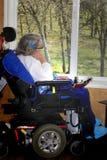 Donna handicappata che guarda fuori finestra fotografia stock