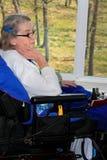 Donna handicappata dalla finestra Immagine Stock